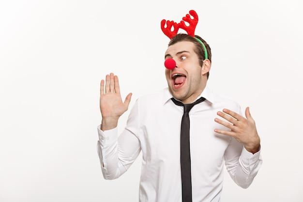Weihnachtskonzept - hübscher geschäftsmann, der rentierhaarband trägt, der lustigen gesichtsausdruck lokalisiert auf weiß macht.