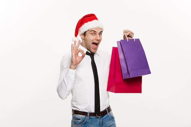 Weihnachtskonzept - hübscher geschäftsmann feiern frohe weihnachten und frohes neues jahr tragen weihnachtsmütze mit einkaufstasche.