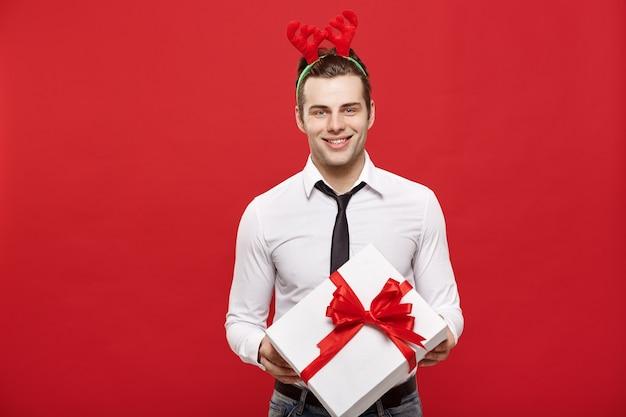 Weihnachtskonzept - hübscher geschäftsmann feiern frohe weihnachten und glückliches neues jahr tragen rentierhaarband und halten weißes geschenk.