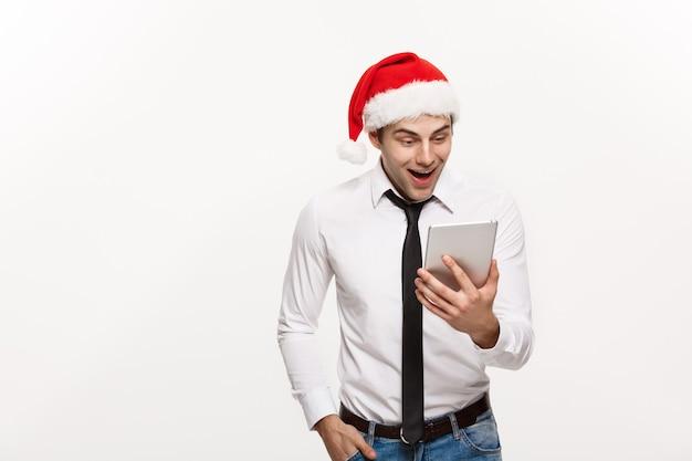 Weihnachtskonzept - hübscher geschäftsmann tragen weihnachtsmütze, die tablette mit überraschendem gesichtsausdruck spielt.