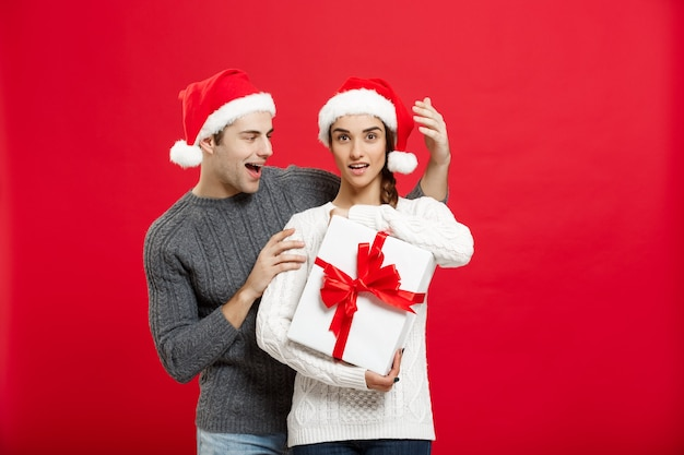 Weihnachtskonzept - hübscher junger freund im pullover überraschen seine freundin mit weißem geschenk.