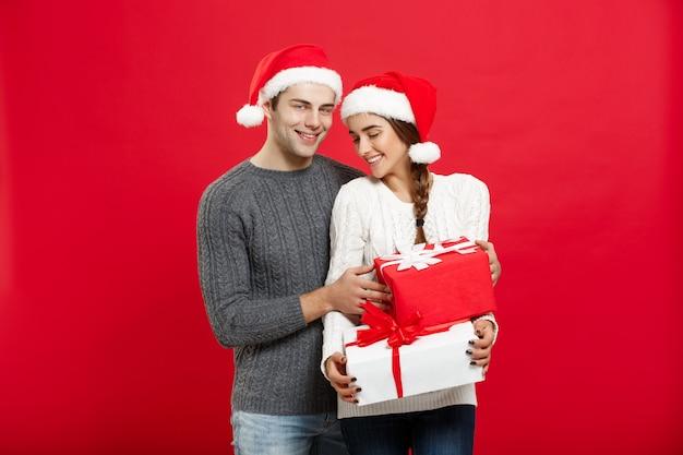 Weihnachtskonzept - hübscher junger freund im weihnachtspullover überraschen seine freundin mit geschenken.