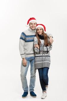 Weihnachtskonzept - in voller länge junges attraktives kaukasisches paar, das eine umarmung gibt, die für weihnachtstag feiert.