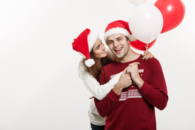Weihnachtskonzept - junge freundin, die ballon hält, umarmt und spielt mit ihrem freund, der an weihnachten eine überraschung tut.