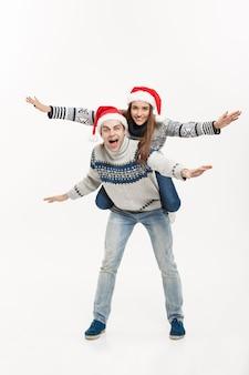 Weihnachtskonzept - junge glückliche paare in voller länge in pullovern, die huckepackfahrt isoliert auf weißer grauer wand genießen.