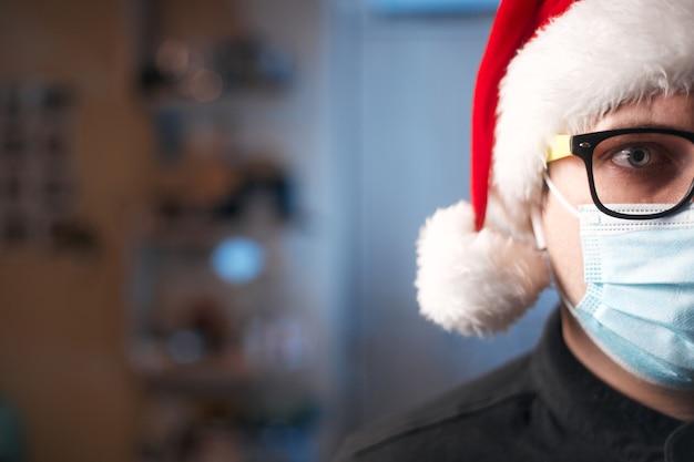 Weihnachtskonzept, kaukasischer mann, der medizinische maske und weihnachtsmütze trägt