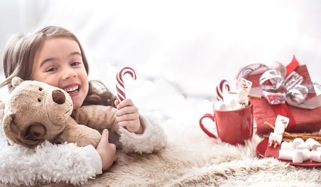 Weihnachtskonzept, kleines niedliches mädchen, das teddybärspielzeug im wohnzimmer mit geschenken auf hellem hintergrund umarmt, platz für text