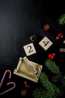 Weihnachtskonzept mit dekorationen, tannenbaumaste, mit kalender am 24. dezember