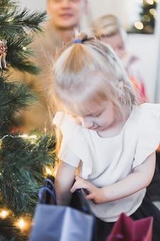 Weihnachtskonzept mit dem mädchen, das in der tasche erreicht