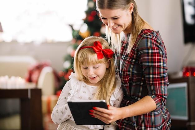 Weihnachtskonzept mit der familie, die tablette betrachtet