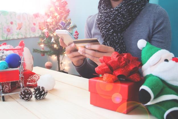 Weihnachtskonzept mit frau, die handy und kreditkarte verwendet