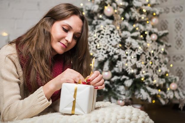 Weihnachtskonzept mit glücklicher frauenöffnungsgeschenkbox