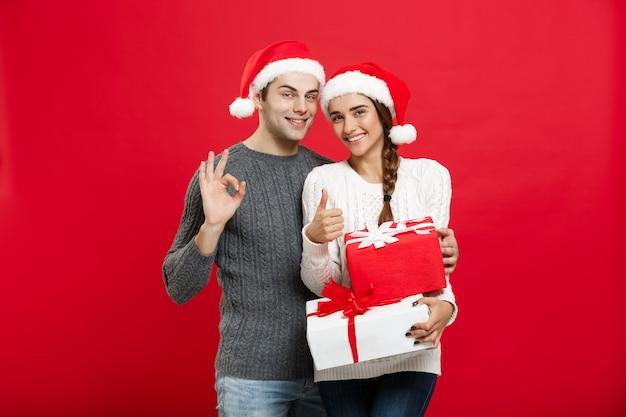 Weihnachtskonzept - porträt des jungen paares im weihnachtspullover, das ok geste mit geschenken zeigt.