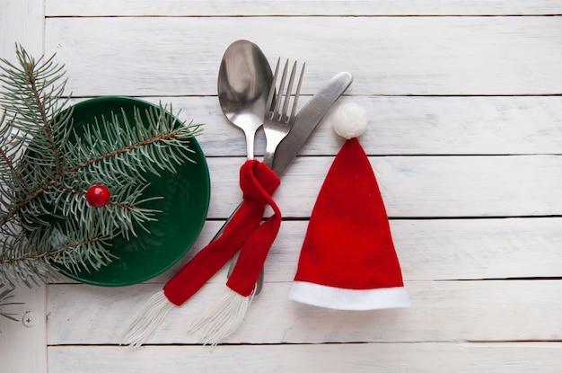 Weihnachtskonzept roter hut und besteck mit einem roten schal auf weißem holzhintergrund gebunden