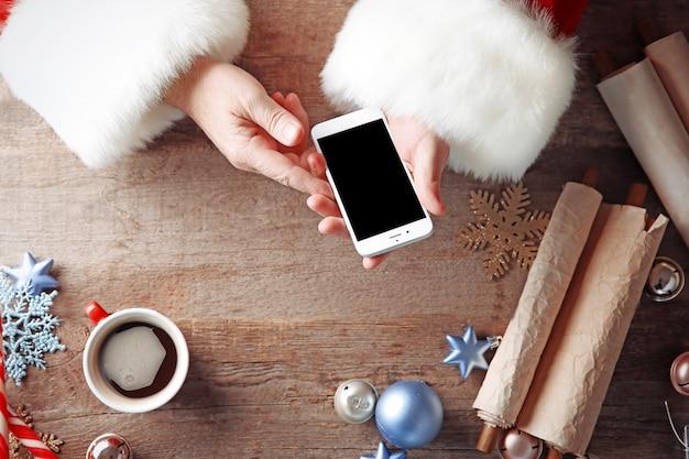 Weihnachtskonzept. santa nimmt smartphone in die hände über holztisch, nahaufnahme