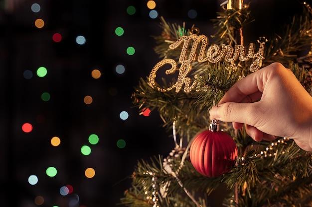Weihnachtskonzept - schöne dekorkugel, die am weihnachtsbaum mit funkelndem lichtfleck hängt