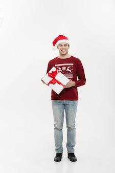 Weihnachtskonzept - schöner junger mann in voller länge im pullover mit weißem weihnachtsgeschenk.
