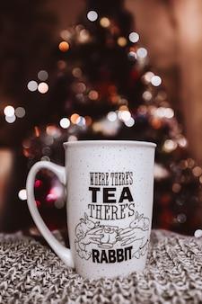 Weihnachtskonzept, tasse stehend auf gestricktem kuscheligem material gegen bokeh unscharfen hintergrund.