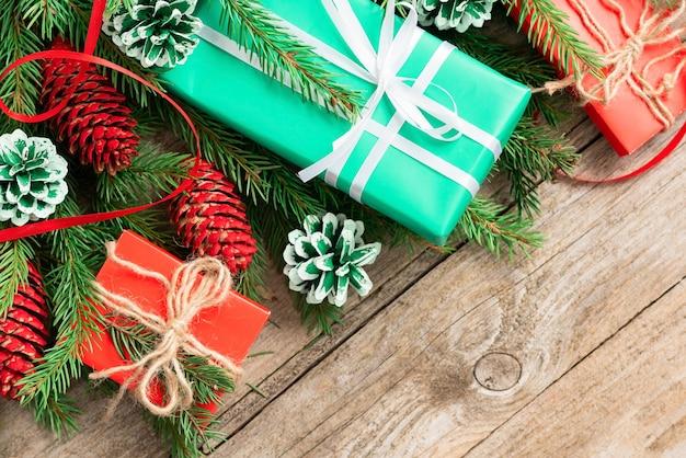 Weihnachtskonzept von geschenken und tannenzweigen mit zapfen.
