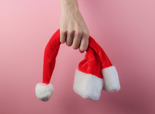 Weihnachtskonzept. weibliche hände halten weihnachtsmütze auf rosa pastellhintergrund