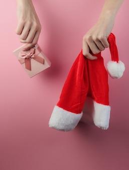 Weihnachtskonzept. weibliche hände halten weihnachtsmütze und geschenkbox auf rosa pastellhintergrund