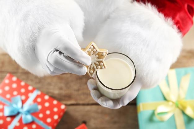 Weihnachtskonzept. weihnachtsmann mit glas milch und keksen in den händen, nahaufnahme