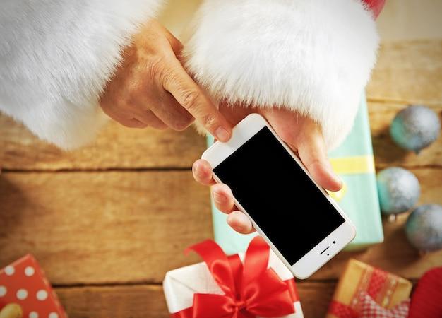 Weihnachtskonzept. weihnachtsmann mit smartphone in den händen, nahaufnahme