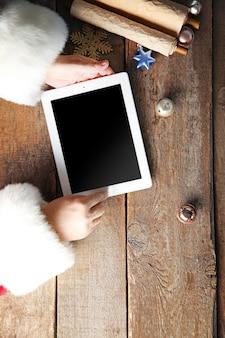 Weihnachtskonzept. weihnachtsmann mit tablet in händen über holztisch, nahaufnahme
