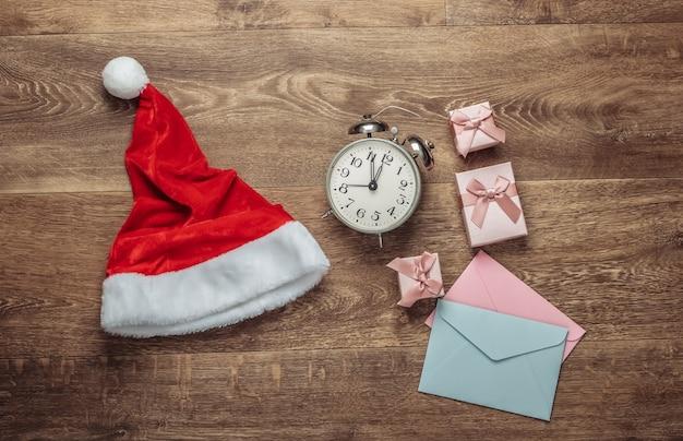 Weihnachtskonzept. weihnachtsmütze, umschläge, geschenkboxen, wecker auf dem boden. draufsicht