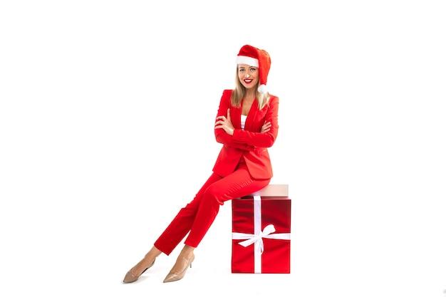Weihnachtskonzeptfoto der eleganten blonden dame im roten anzug und in den hohen absätzen, die auf verpackter geschenkbox sitzen. winterferienkonzept