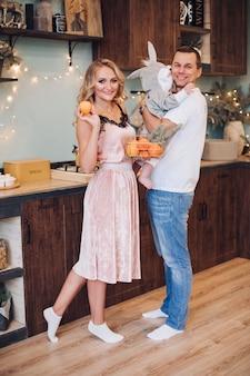 Weihnachtskonzeptfoto der freudigen kleinen familie des mannes, der frau und des babys, die in der gut eingerichteten küche aufwerfen. urlaubskonzept