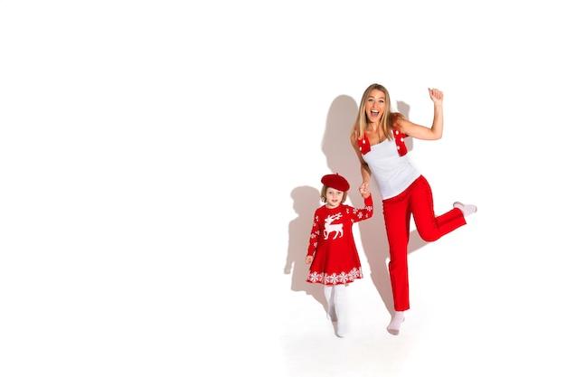 Weihnachtskonzeptfoto des kleinen mädchens im roten kleid, das hände mit einer aufgeregten blonden frau beim winken in der kamera hält