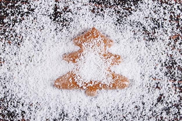 Weihnachtskonzepthintergrund, handgemachter lebkuchen in form eines weihnachtsbaums auf einem holztisch, frustriert durch weißen schnee