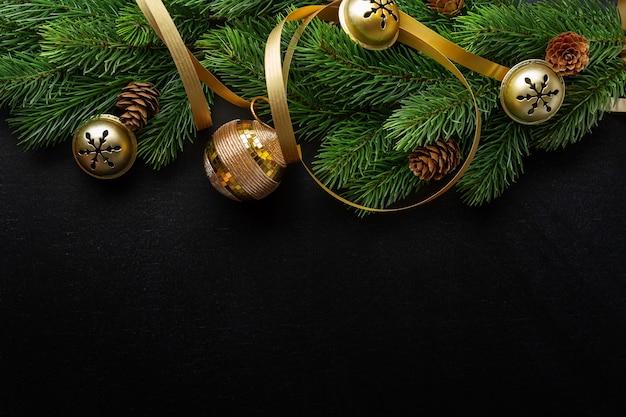 Weihnachtskonzeptioneller hintergrund mit kugeln und tannenzweigen auf dunkelheit. ansicht von oben