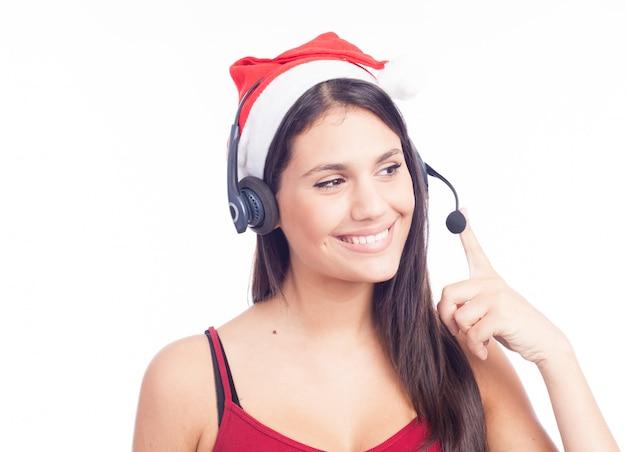 Weihnachtskopfhörerfrau vom telemarketing-kundenkontaktcenter, welches das unterhaltungslächeln roten sankt-hutes trägt