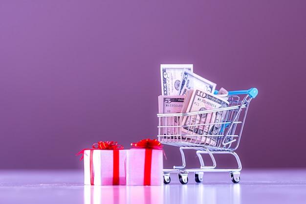 Weihnachtskostenplanungskonzept, geschenkboxen und einkaufswagen voller geld, bild in lila ton