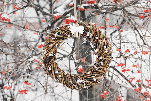Weihnachtskranz am baum. handgemachter kranz an der tür auf einem hintergrund der winterbeeren. winterdekor. winterviburnum