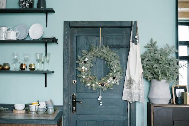 Weihnachtskranz an der holztür in der küche im skandinavischen stil in blautönen