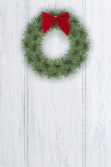 Weihnachtskranz an der tür. weihnachtshintergrund, hauptdekoration auf weißer holztür. vertikales format mit kopienraum.