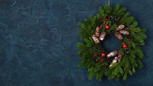 Weihnachtskranz auf blauem wandhintergrund