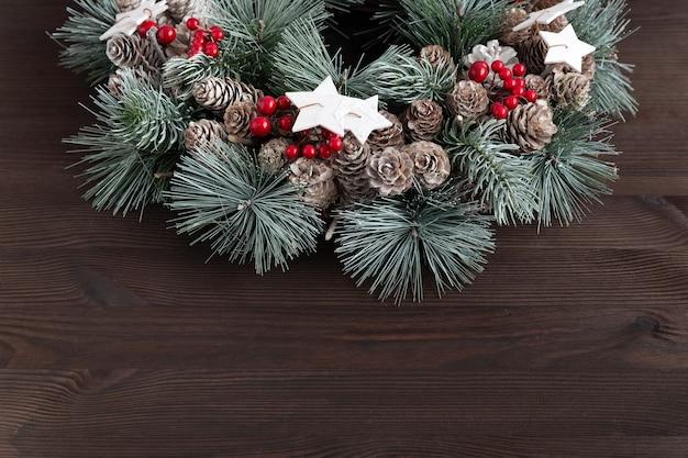 Weihnachtskranz auf dunklem hölzernem hintergrund. neujahrsmuster. speicherplatz kopieren.