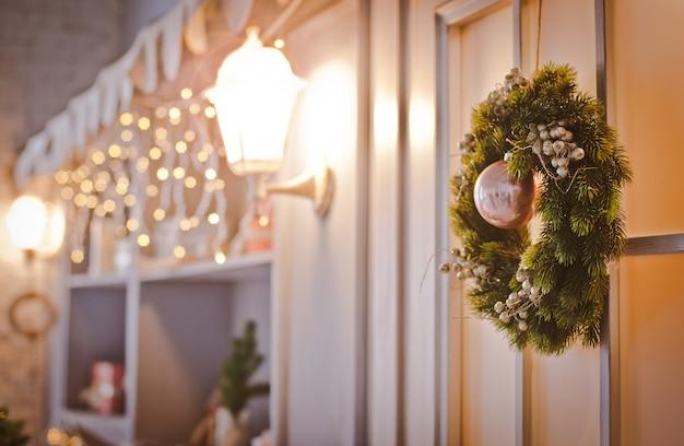 Weihnachtskranz auf einer tür mit stoß und einer kugel horizontal