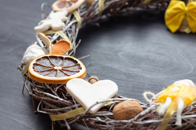 Weihnachtskranz aus birkenzweigen, getrockneten zitrusfrüchten, tonfiguren (herz, bär), nüssen, eichel und gelber schleife, mit goldenem band zusammengebunden. nahansicht.