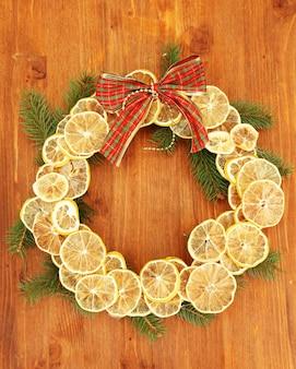 Weihnachtskranz aus getrockneten zitronen mit tannenbaum und bogen auf holztisch
