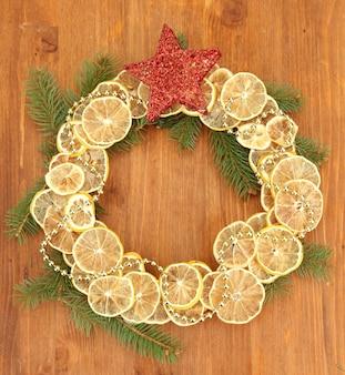 Weihnachtskranz aus getrockneten zitronen mit tannenbaum und stern auf holzoberfläche