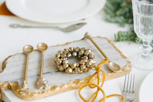 Weihnachtskranz aus goldenen glocken in der dekoration des festlichen abendessens. besteck auf einem marmorbrett