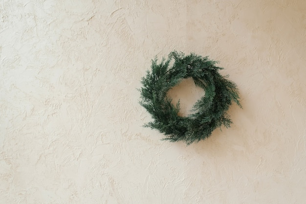Weihnachtskranz aus nadelholz auf beigem hintergrund mit kopierraum
