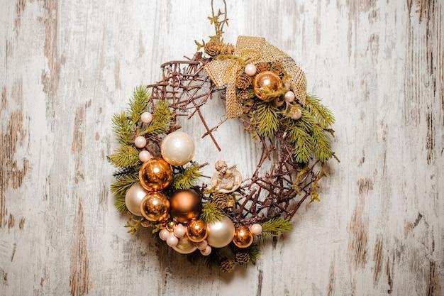 Weihnachtskranz aus tannenbaum und zweigen mit goldenen glaskugeln und schleife