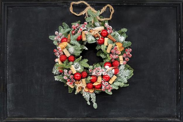 Weihnachtskranz aus tannenzweigen, getrockneten äpfeln, zimt, roten beeren, flaschenverschlüssen, roten kugeln, die an einer schwarzen tafel hängen.