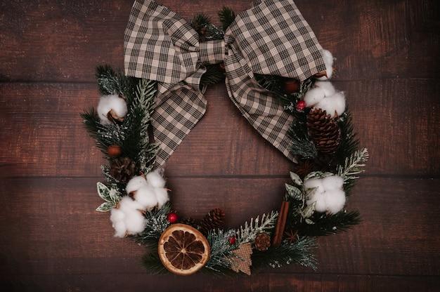 Weihnachtskranz aus weihnachtsschmuck, zapfen, gewürzen auf holzhintergrund. im flatley-stil. das konzept, das neue jahr zu feiern. ansicht von oben.